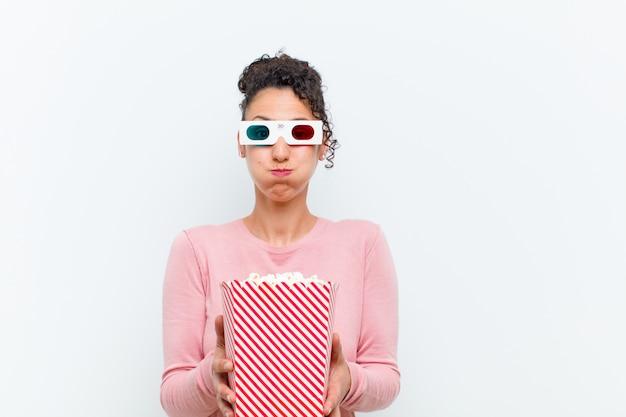 Jeune jolie femme avec des pop corn et des lunettes 3d contre un mur blanc