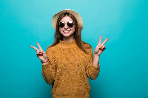 Jeune jolie femme portant chapeau et lunettes de soleil a souligné le geste de paix sur le mur bleu