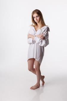Jeune jolie femme portant une chemise qui pose en studio avec les pieds nus, les tests de modèle