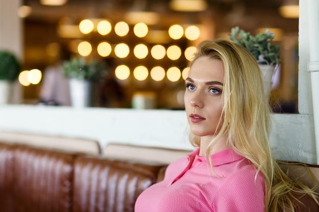 Jeune jolie femme portant en polo rose reposant dans un café