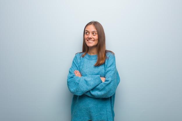 Jeune jolie femme portant un pull bleu souriant confiant et croisant les bras, levant