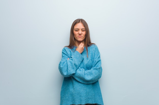 Jeune jolie femme portant un pull bleu toussant, malade à cause d'un virus ou d'une infection