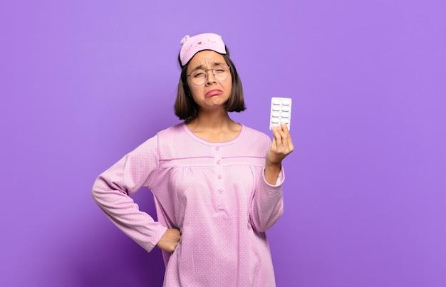 Jeune jolie femme portant des pyjamas et tenant des pilules