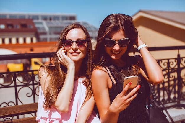 Jeune jolie femme posant dans la rue avec un téléphone
