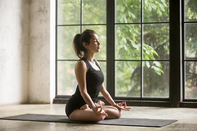Jeune jolie femme en pose de padmasana, fond de studio