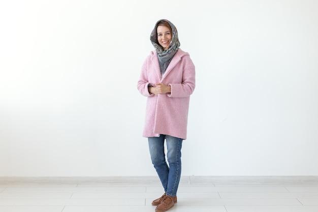 Jeune jolie femme positive posant dans une écharpe et un manteau rose sur fond blanc. concept de vêtements de printemps automne. espace publicitaire.