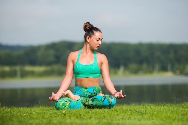 Jeune jolie femme en posture de lotus dans le parc