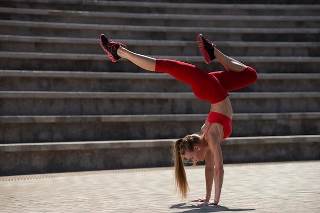 Jeune jolie femme pratiquant le yoga en plein air