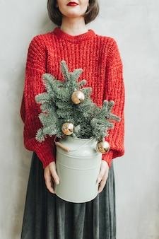 Jeune jolie femme avec pull tricoté rouge et jupe grise tenant l'arbre de noël décoré de boules d'or