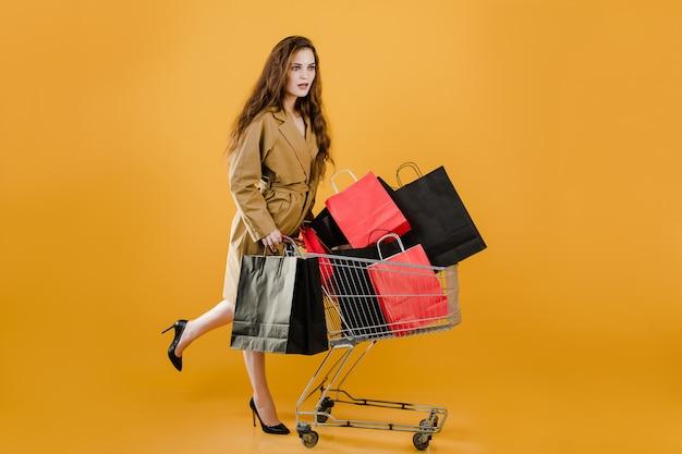 Jeune jolie femme a pushcart avec des sacs colorés et ruban de signalisation isolé sur jaune