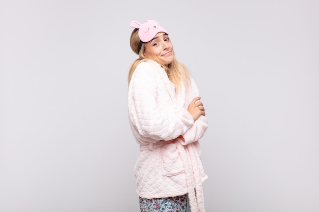 Jeune jolie femme en pyjama, haussant les épaules, se sentant confuse et incertaine, doutant les bras croisés et le regard perplexe