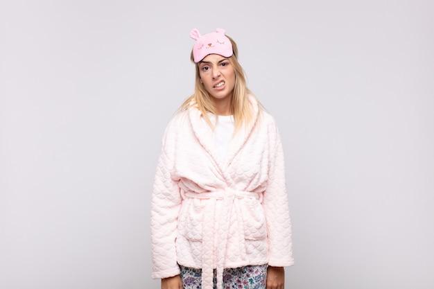 Jeune jolie femme en pyjama, se sentant perplexe et confus, avec une expression stupide et stupéfaite en regardant quelque chose d'inattendu
