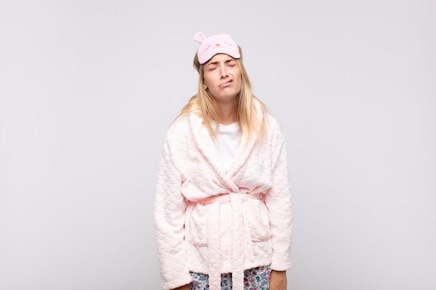 Jeune jolie femme en pyjama, se sentant triste et pleurnichard avec un regard malheureux, pleurant avec une attitude négative et frustrée