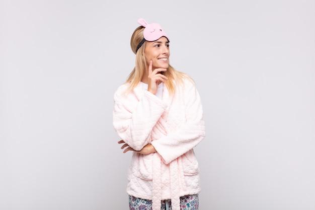 Jeune jolie femme en pyjama, souriant joyeusement et rêvassant ou doutant, regardant sur le côté