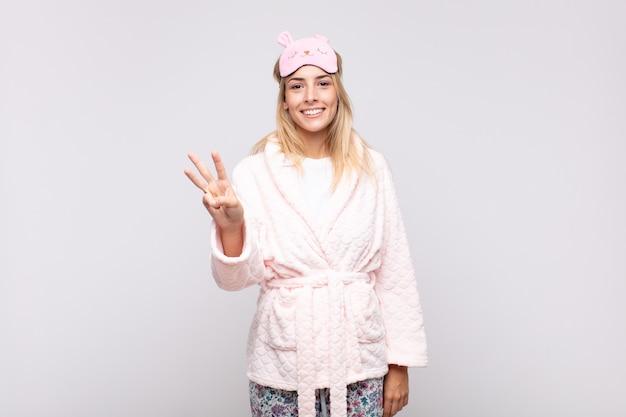 Jeune jolie femme en pyjama, souriant et à la recherche amicale, montrant le numéro trois ou troisième