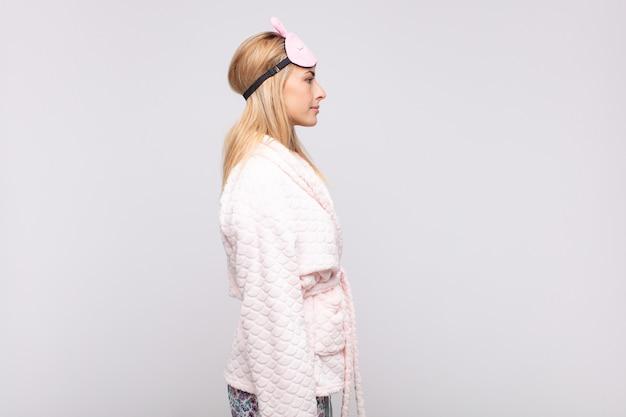 Jeune jolie femme en pyjama, vue de profil cherchant à copier l'espace devant, pensant, imaginant ou rêvant