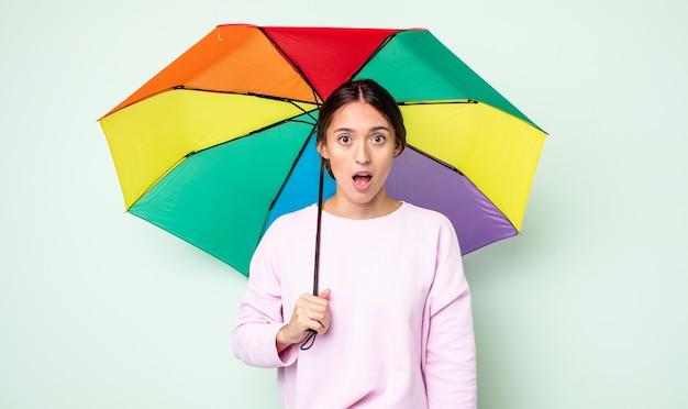 Jeune jolie femme qui a l'air très choquée ou surprise. concept de parapluie