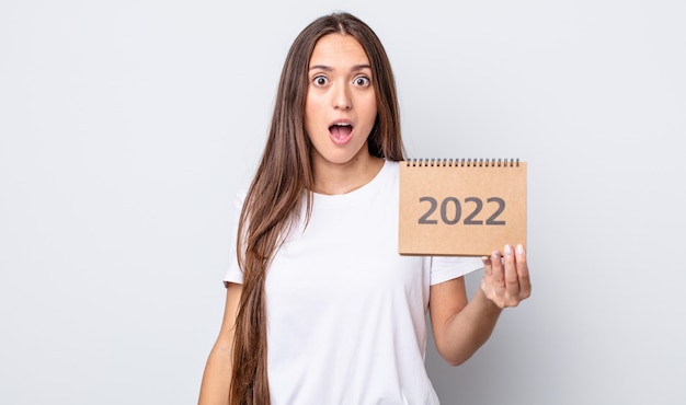 Jeune jolie femme qui a l'air très choquée ou surprise. concept de planificateur 2022
