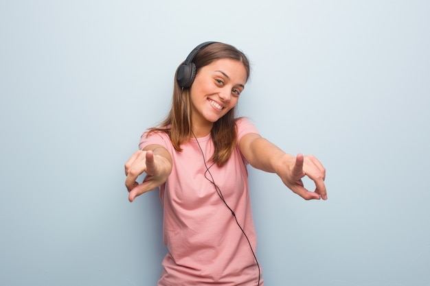 Jeune jolie femme de race blanche gaie et souriante pointant vers l'avant. elle écoute de la musique avec des écouteurs.