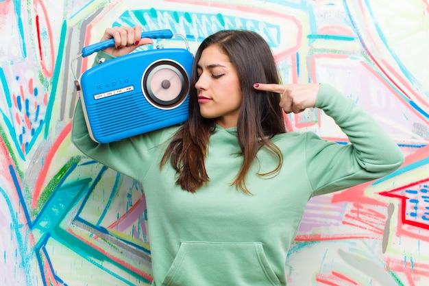 Jeune jolie femme avec une radio vintage contre le mur de graffitis