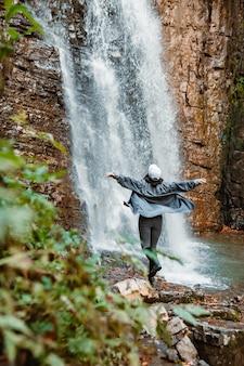 Jeune jolie femme randonnée profitant de la vue sur l'espace de copie de la cascade