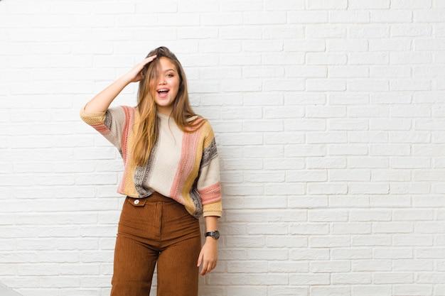 Jeune jolie femme à la recherche de bonheur, étonné et surpris, souriant et réalisant une bonne nouvelle incroyable et incroyable contre le mur de briques