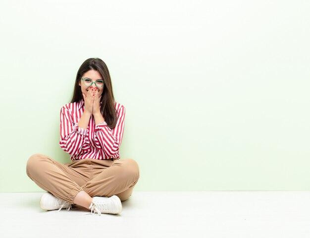 Jeune jolie femme à la recherche de bouche couvrant heureuse, joyeuse, chanceuse et surprise avec les deux mains assis sur le sol