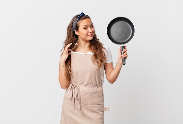 Jeune jolie femme à la recherche d'un concept de chef arrogant, réussi, positif et fier et tenant une casserole