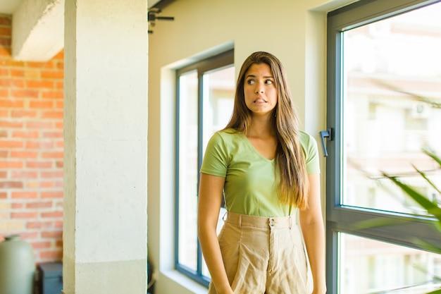 Jeune jolie femme à la recherche inquiète, stressée, anxieuse et effrayée, paniquée et serrant les dents