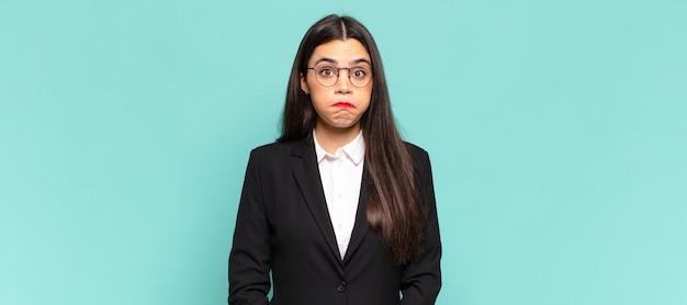 Jeune jolie femme à la recherche maladroite et drôle avec une expression idiote aux yeux croisés, plaisantant et s'amusant. concept d'entreprise