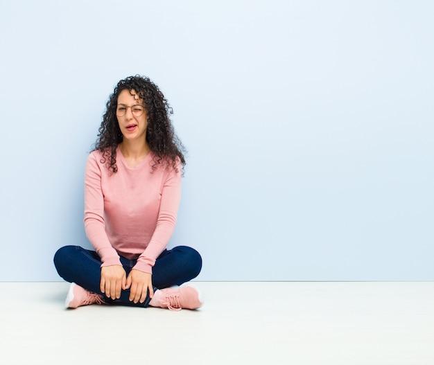 Jeune jolie femme à la recherche de plaisir et de convivialité, souriant et un clin d'œil à vous avec une attitude positive assis sur le sol