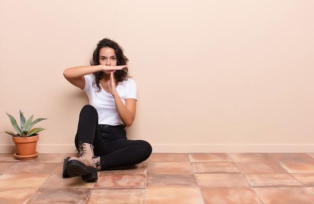 Jeune jolie femme à la recherche sérieuse, sévère, en colère et mécontente, faisant signe de temps mort assis sur un sol en terrasse