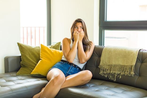 Jeune jolie femme à la recherche de soucis, anxieux, stressés et effrayés, se ronger les ongles et à la recherche de l'espace de copie latérale