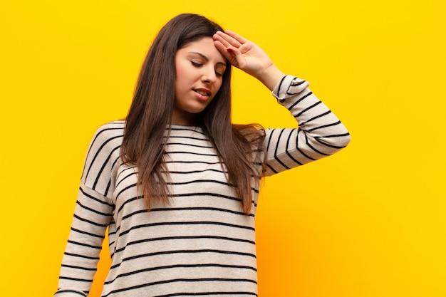 Jeune jolie femme à la recherche de stress, de fatigue et de frustration, séchant la sueur sur le front, se sentant désespérée et épuisée contre le mur jaune