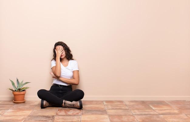 Jeune jolie femme à la recherche de stress, honte avec un mal de tête, couvrant le visage avec la main assis sur le sol d'une terrasse