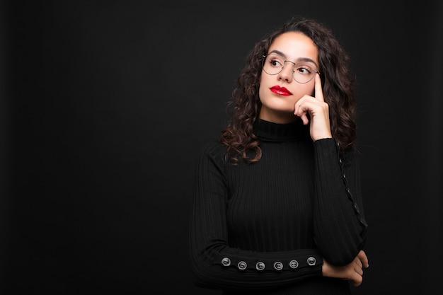 Jeune jolie femme avec un regard concentré, se demandant avec une expression douteuse, levant les yeux et sur le côté contre le mur noir.