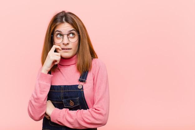 Jeune jolie femme avec un regard surpris, nerveux, inquiet ou effrayé, regardant sur le côté vers l'espace de copie sur le mur rose
