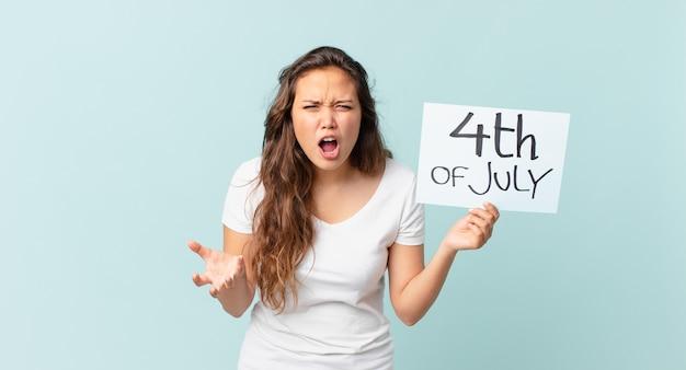 Jeune jolie femme regardant le concept de fête de l'indépendance en colère, agacé et frustré