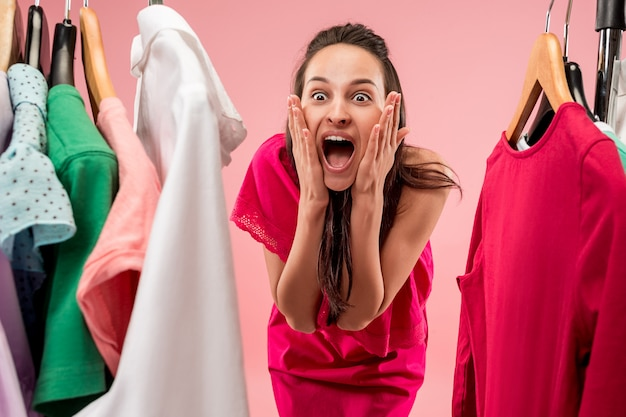 La jeune jolie femme regardant des robes et l'essaie tout en choisissant au magasin