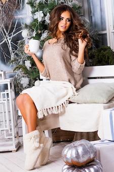 Jeune jolie femme rêvant et buvant du café ou du thé, profitant du matin de noël, gros plan portrait de belle dame dans des vêtements chauds et confortables assis sur une terrasse décorée de lumière