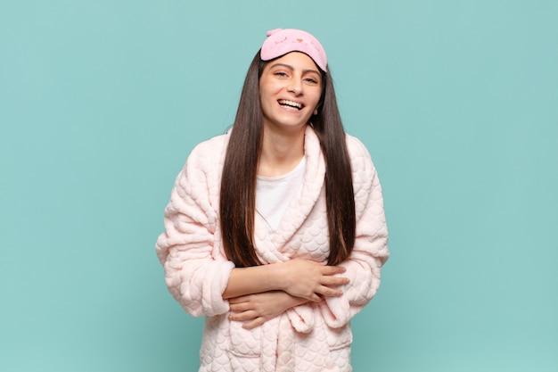 Jeune jolie femme riant aux éclats d'une blague hilarante, se sentant heureuse et joyeuse, s'amusant. concept de réveil en pyjama
