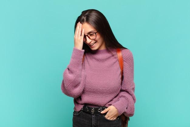 Jeune jolie femme riant et giflant le front comme disant doh ! j'ai oublié ou c'était une erreur stupide. concept d'étudiant