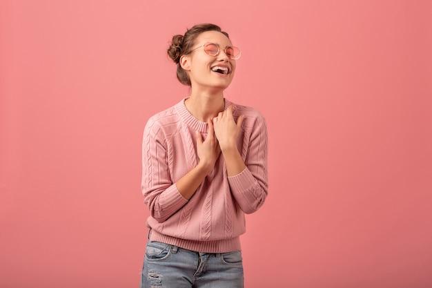Jeune jolie femme riante sortie en pull rose et lunettes de soleil isolé sur fond rose studio