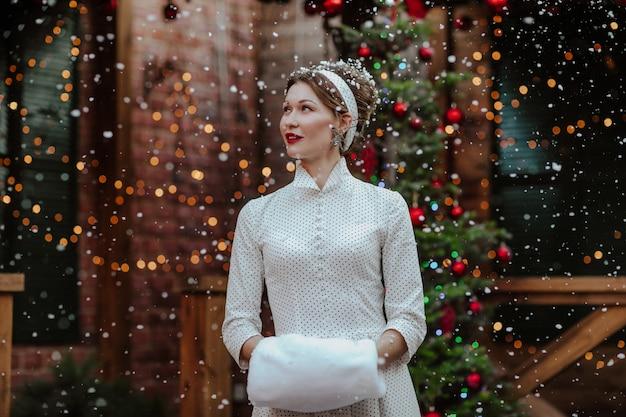 Jeune jolie femme en robe blanche de style rétro et coiffure avec ruban posant sous la neige dans la cour arrière avec arbre et fond de noël.