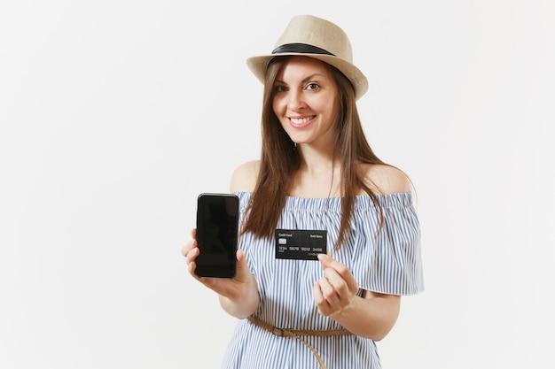 Jeune jolie femme en robe bleue, chapeau montrant un téléphone portable avec appareil photo avec écran vide noir vide, tenant une carte de crédit isolée sur fond blanc. personnes, concept bancaire. espace publicitaire. espace de copie