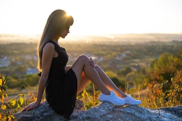 Jeune jolie femme en robe d'été courte noire assise sur un rocher relaxant à l'extérieur au coucher du soleil. femme à la mode profitant d'une soirée chaude dans la nature.