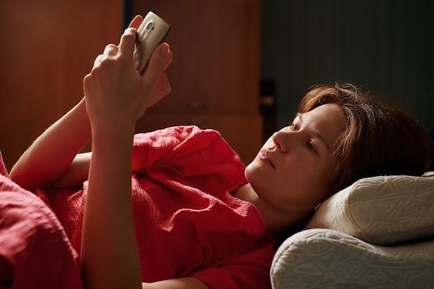 Jeune jolie femme en robe rouge allongée sur le lit et à l'aide de smartphone au soir