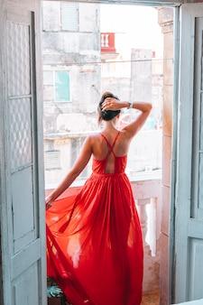 Jeune jolie femme en robe rouge sur l'ancien balcon dans l'appartement à la havane