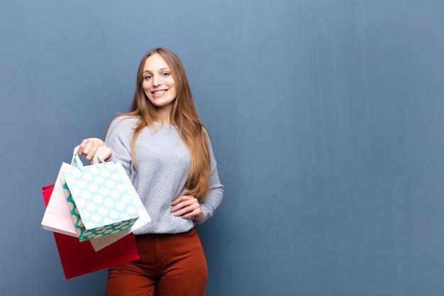 Jeune jolie femme avec des sacs à provisions contre le mur bleu avec une surface