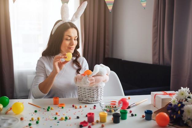 Jeune jolie femme se prépare pour pâques. elle s'assoit et décore le panier et le lapin avec des œufs colorés. décoration et bonbons sur table. le mannequin porte des oreilles artificielles de lapin.